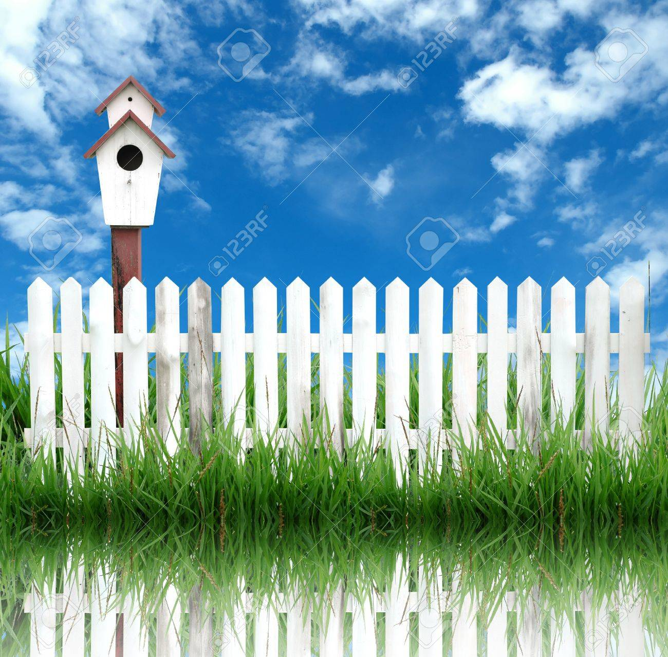birdhouse with white fence and blue sky Stock Photo - 8393239
