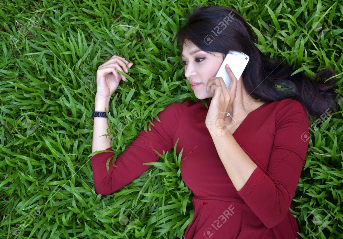 pretty woman making a phone call in the garden Stock Photo - 16141436