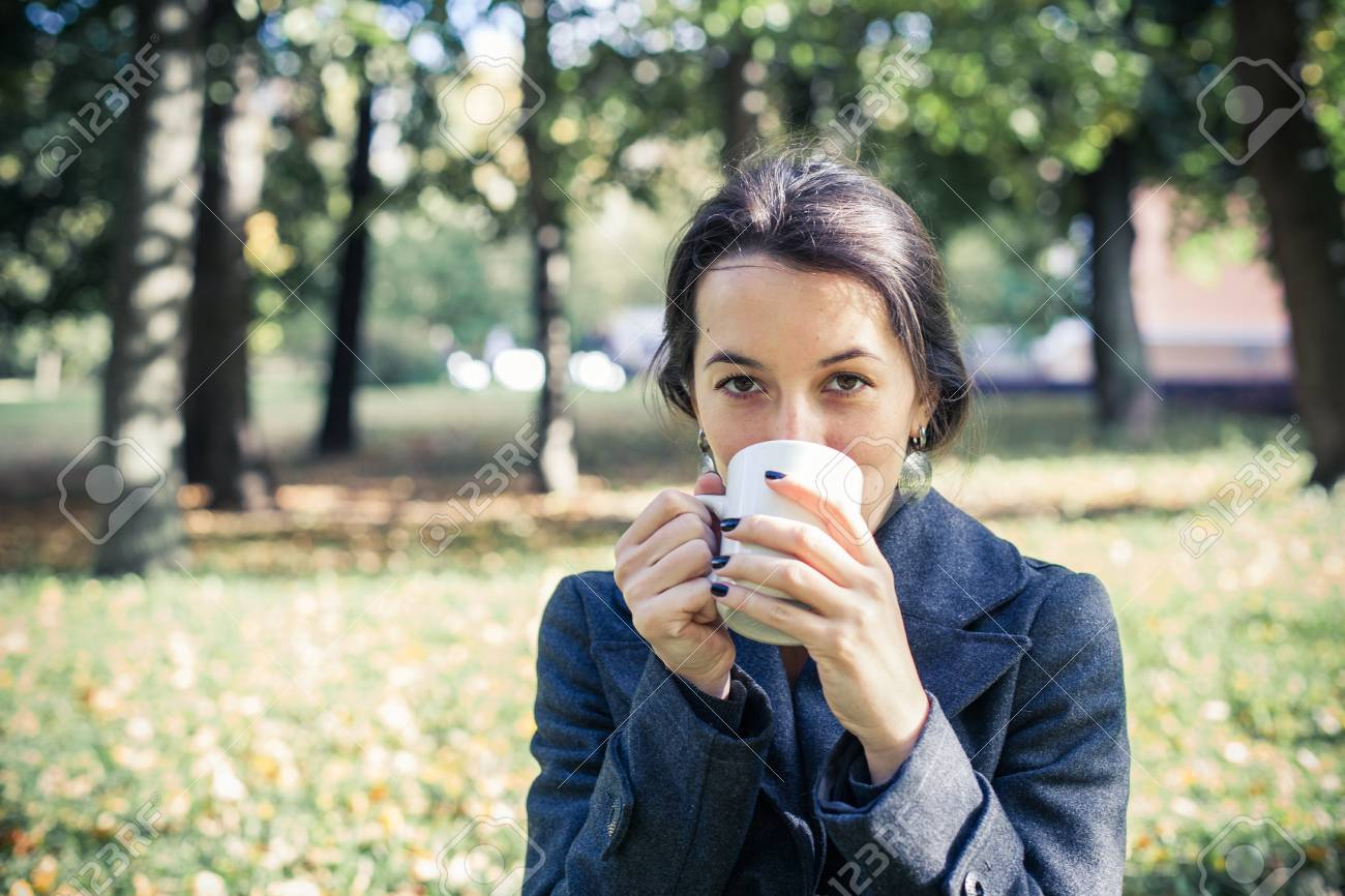 Girl in an autumn part with a white cup of hot drink Stock Photo - 17242108