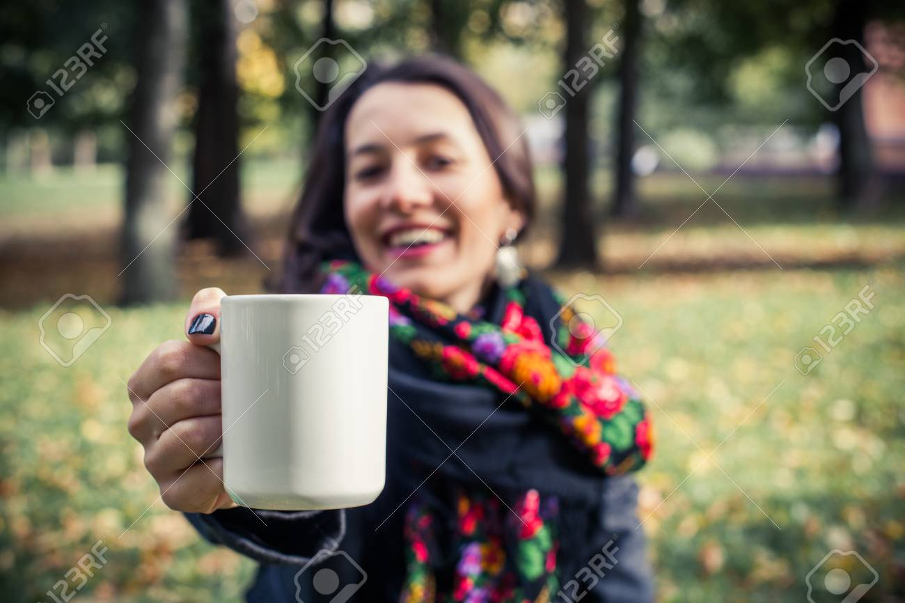 Girl in an autumn part with a white cup of hot drink Stock Photo - 17242105