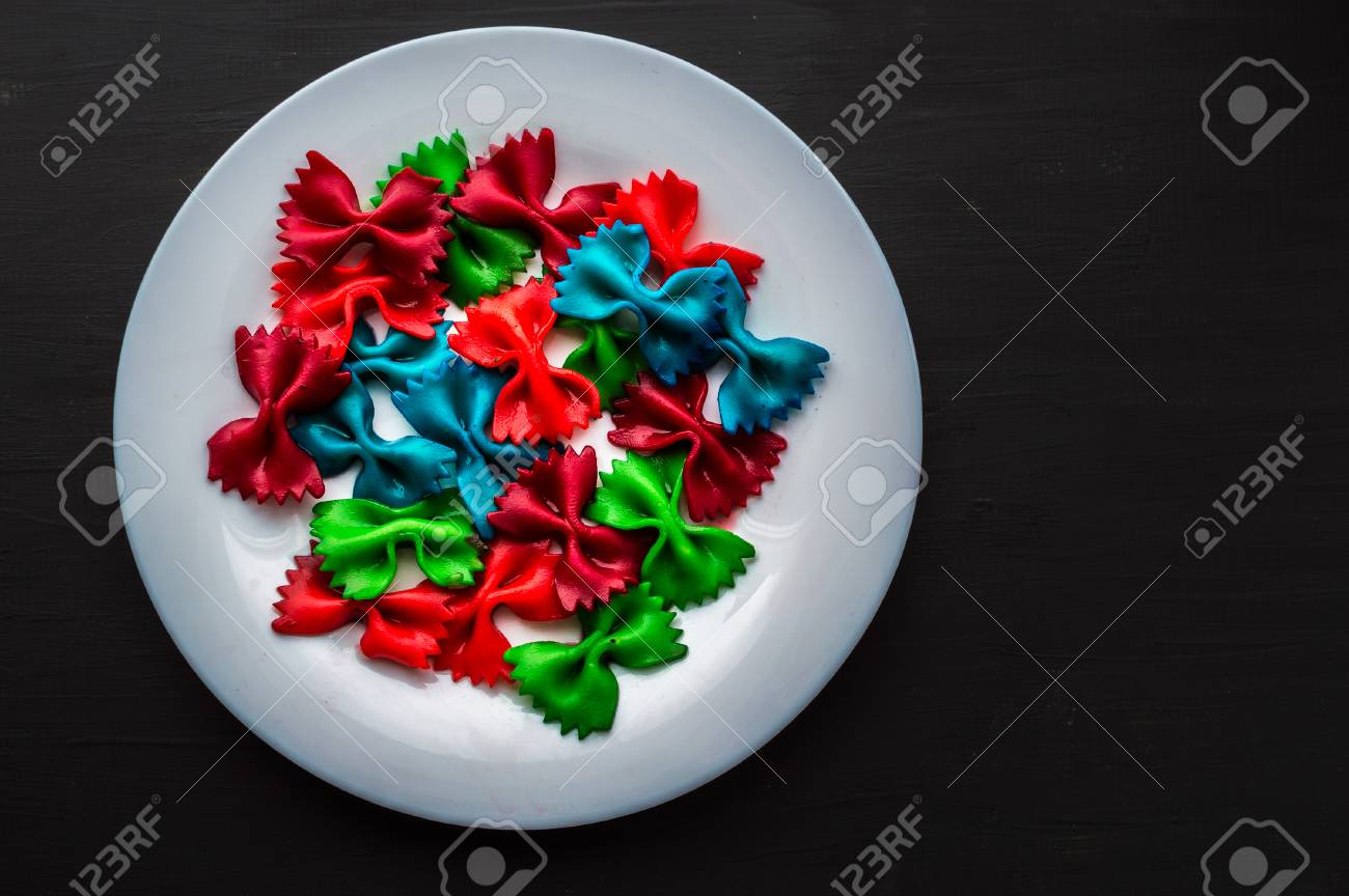 Colored Pasta In A White Plate On A Black Background Food