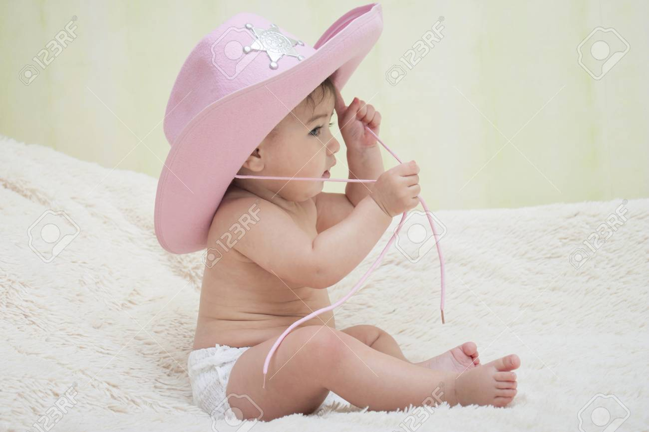 43f251de902e2 baby sitting in a pink cowboy hat Stock Photo - 78943546