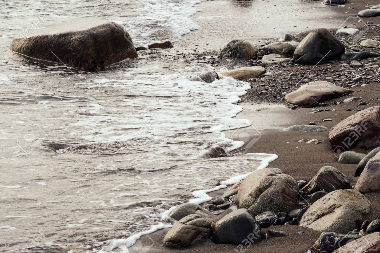Beautiful natural landscape. Sea water covers the beach. Wet stones. Brown color. - 103316393