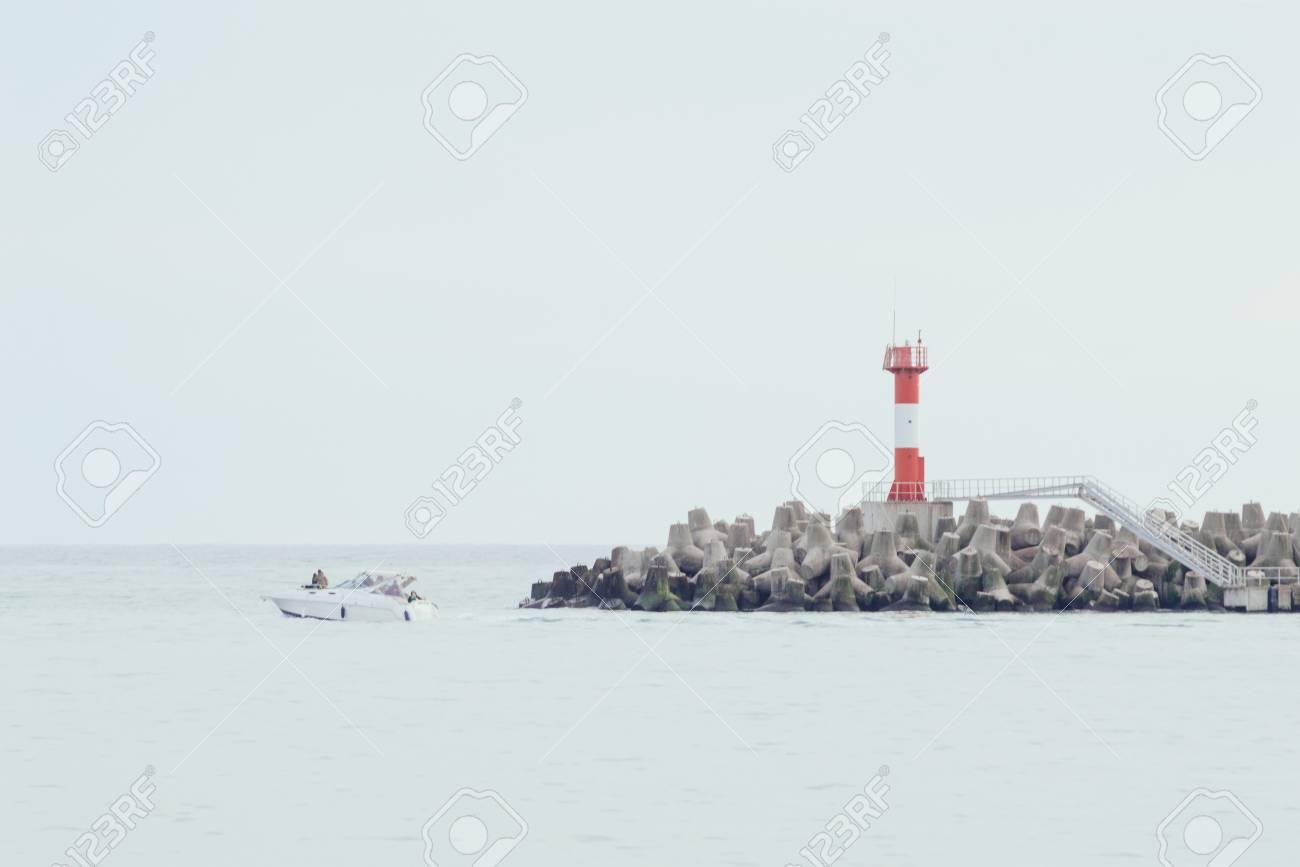 Lighthouse on breakwaters. Boat floating on the waves. Horizontal beautiful background image - 103505341