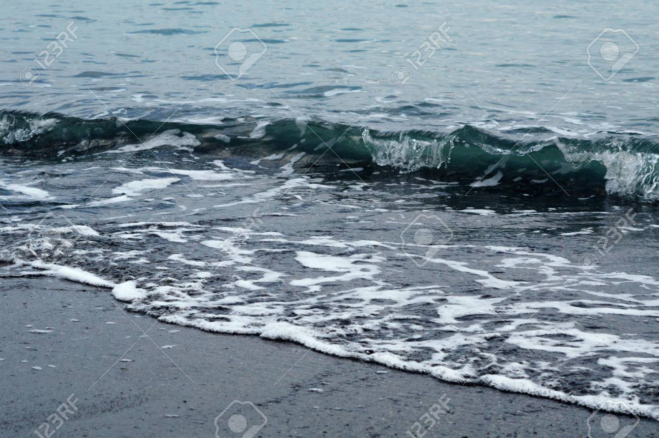 Wave on the shore. Background image in dark colors. Pebble beach. - 103505347