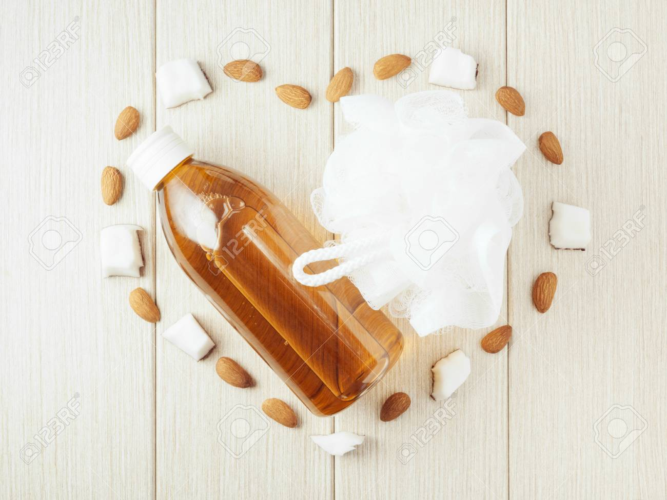 Composition with plastic bottle and mesh shower sponge for body care and beauty products. Beautiful background with almond and coconut. - 112033054