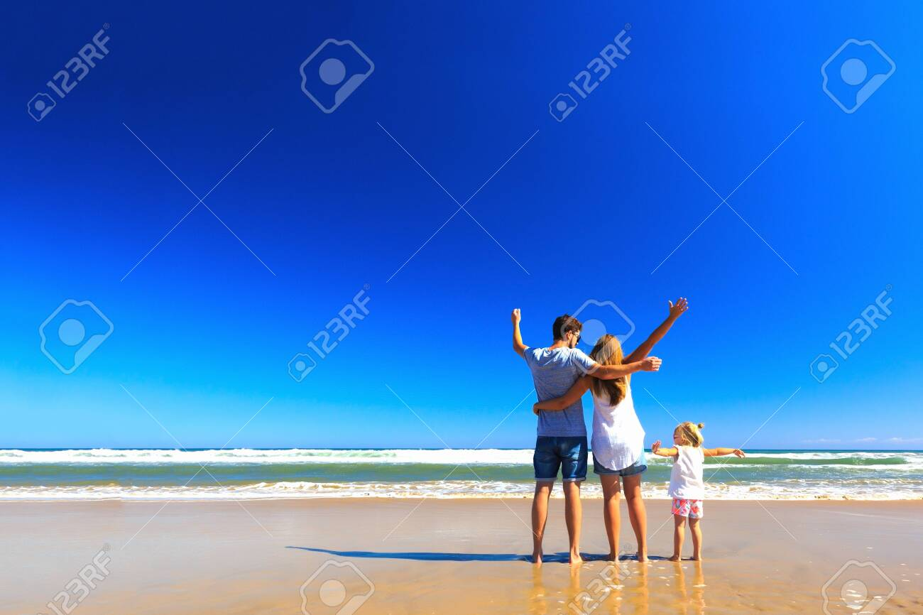 Happy father mother and little stand on the sea shore on a sunny day.COpy space, back view. - 129404087