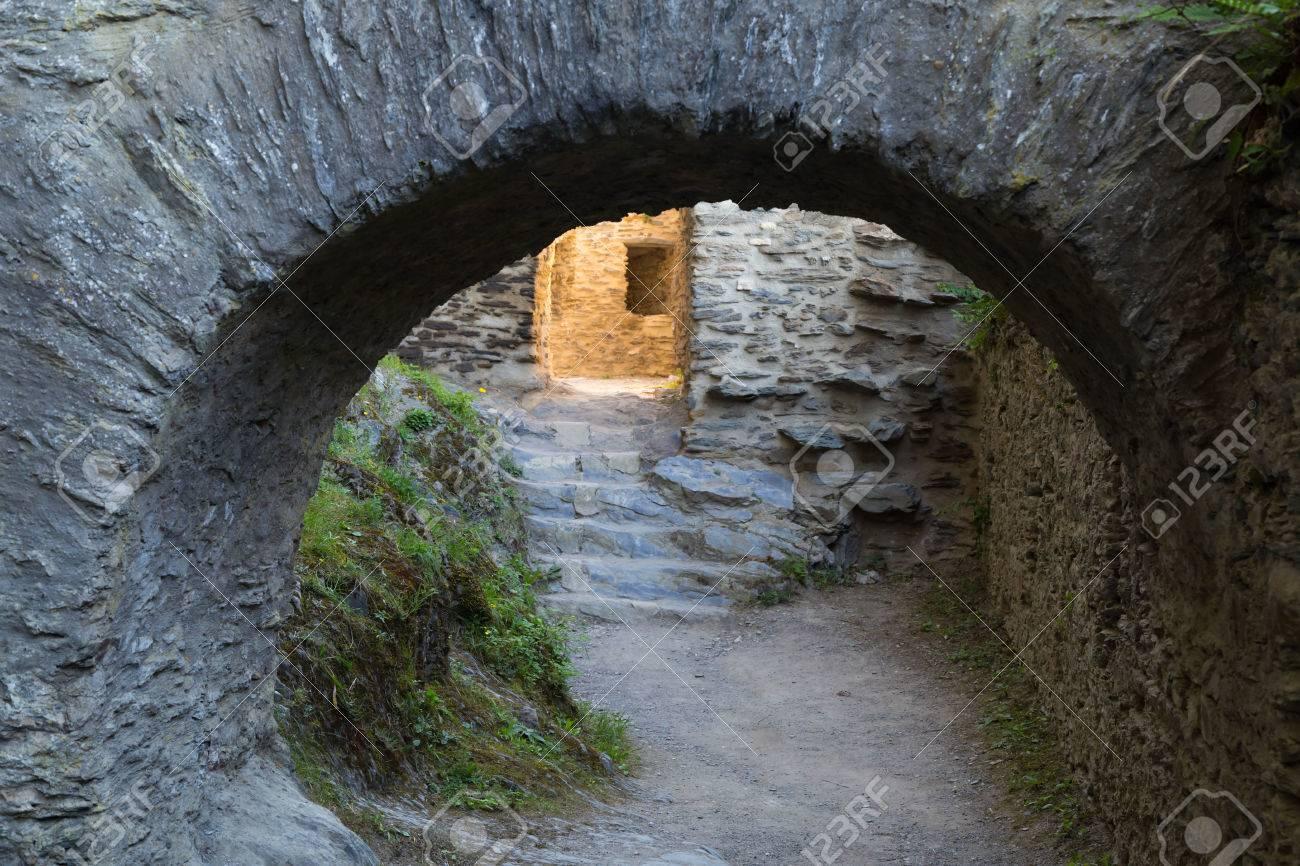 Stenen gang in de ruïnes van het oude kasteel. fragment van fortmuur