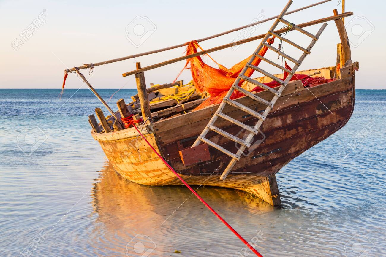 National traditional wooden African boat closeup in shallow water