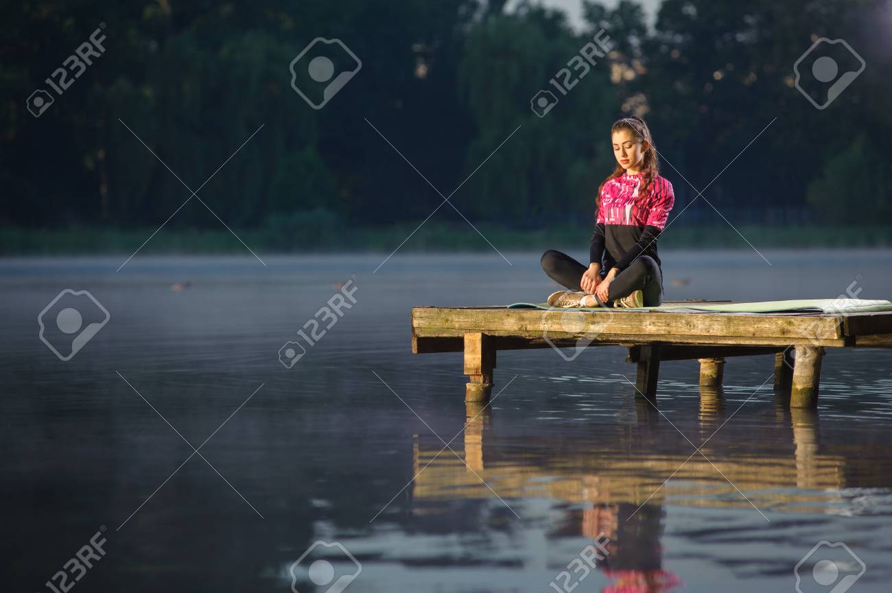 Beautiful young female sitting quietly with her legs crossed in nature on the river, with her eyes closed. Meditation - 69816347