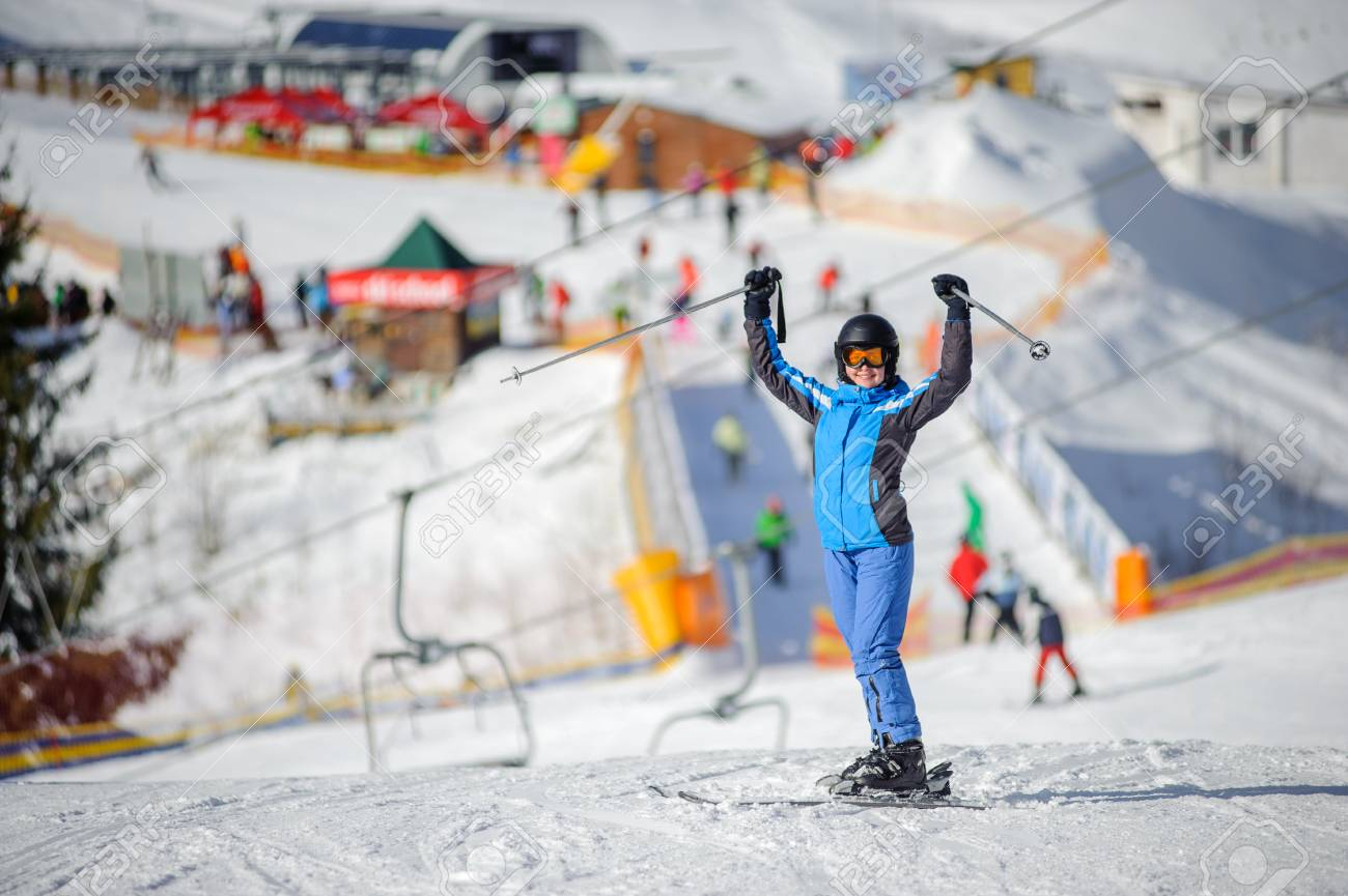 full length portrait of happy girl skier standing with arms up