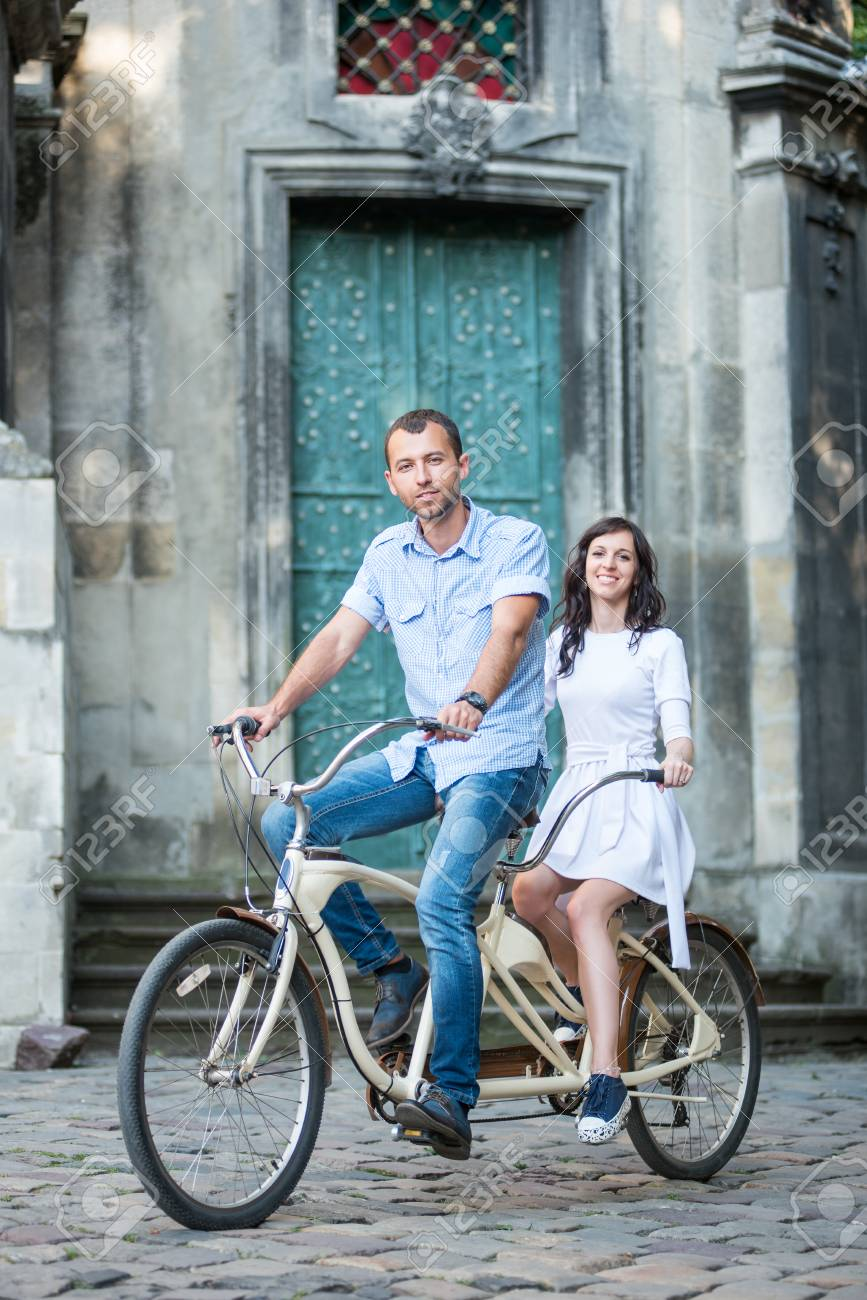 Happy couple riding on vintage tandem bicycle against the backdrop of historic building. They smiling and looking to the camera. Lviv, Ukraine - 70622214