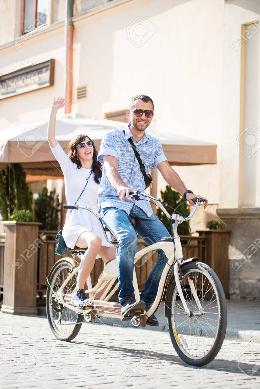 Young couple in sunglasses riding on tandem bicycle on the city at the sunny day. The man runs a bicycle, a girl waving hand - 70622140