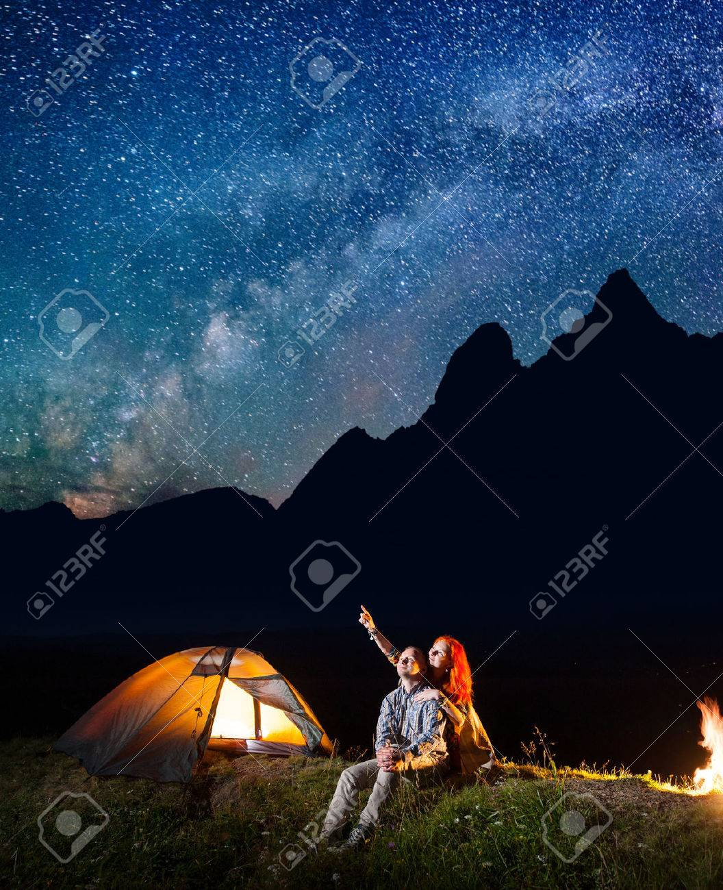 Young tourists man and woman looking at the shines starry sky at night. Happy couple sitting near tent and campfire. Milky way and mountains on the background - 70624736