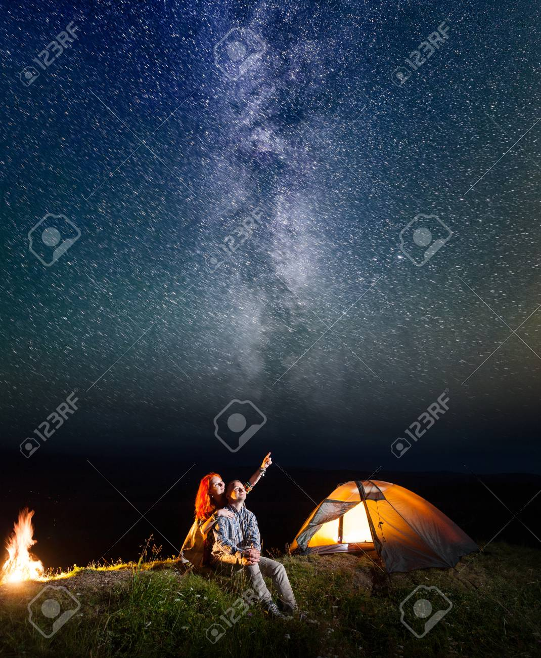 Two lovers - girl and guy looking at the shines starry sky at night. Loving couple sitting near tent and campfire. Long exposure - 77814936