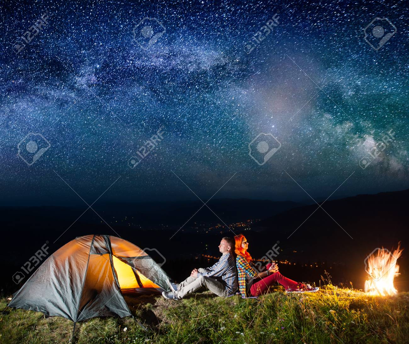 Romantic couple sitting by bonfire near glowing tent under incredibly beautiful starry sky. On the & Romantic Couple Sitting By Bonfire Near Glowing Tent Under ...