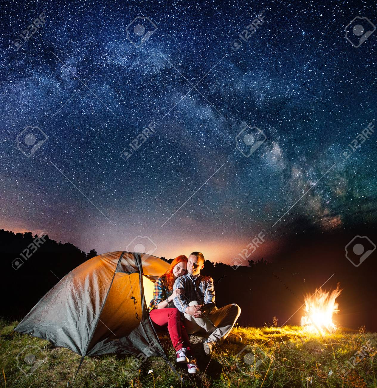 Night camping. Romantic couple sitting in front tent near campfire under shines starry sky and Milky way. Long exposure - 77775889