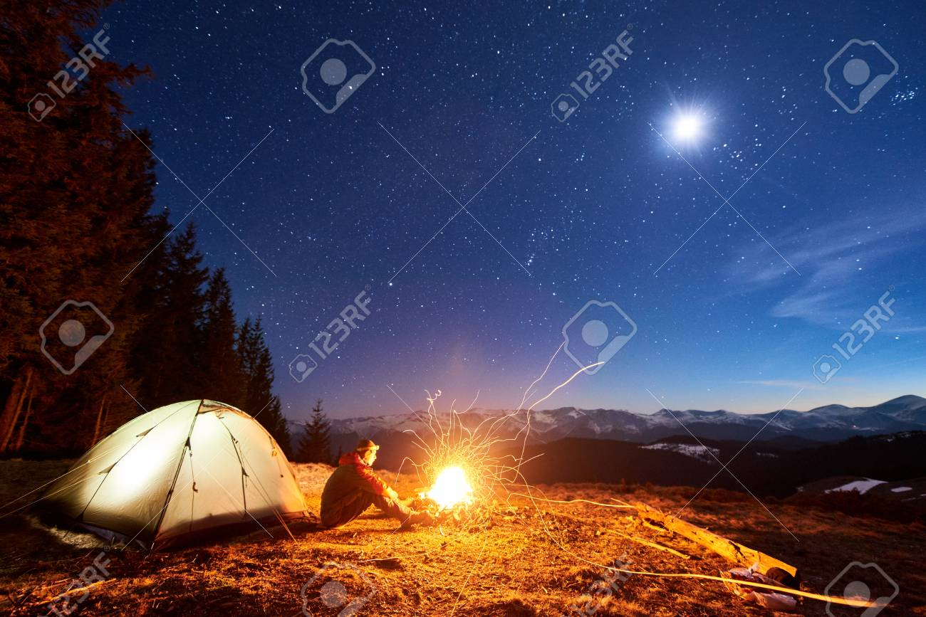 Male tourist have a rest in his camp at night, sitting near campfire and tent under beautiful night sky full of stars and the moon and enjoying night scene in the mountains - 80507768