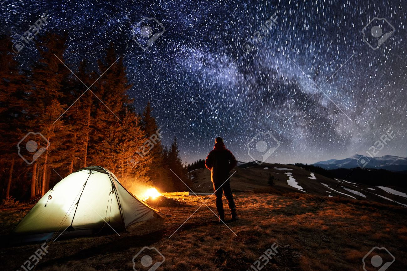 Male tourist have a rest in his camp near the forest at night. Man standing near campfire and tent under beautiful night sky full of stars and milky way, and enjoying night scene. Long exposure - 80507834