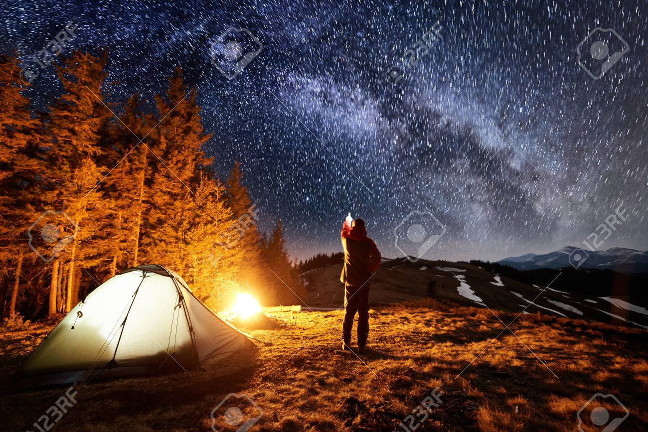 Male tourist have a rest in his camp near the forest at night. Man standing near campfire and tent, pointing at beautiful night sky full of stars and milky way - 80627127