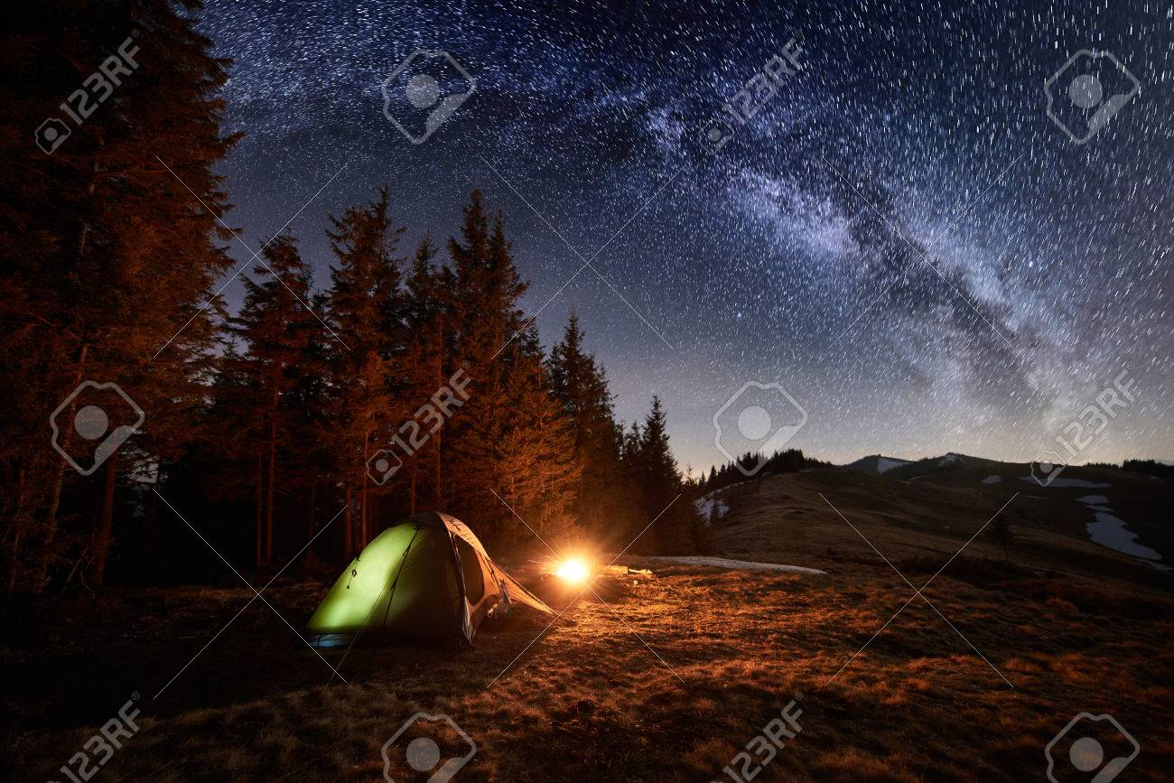 Night camping. Illuminated tent and campfire near forest under beautiful night sky full of stars and milky way - 80698766