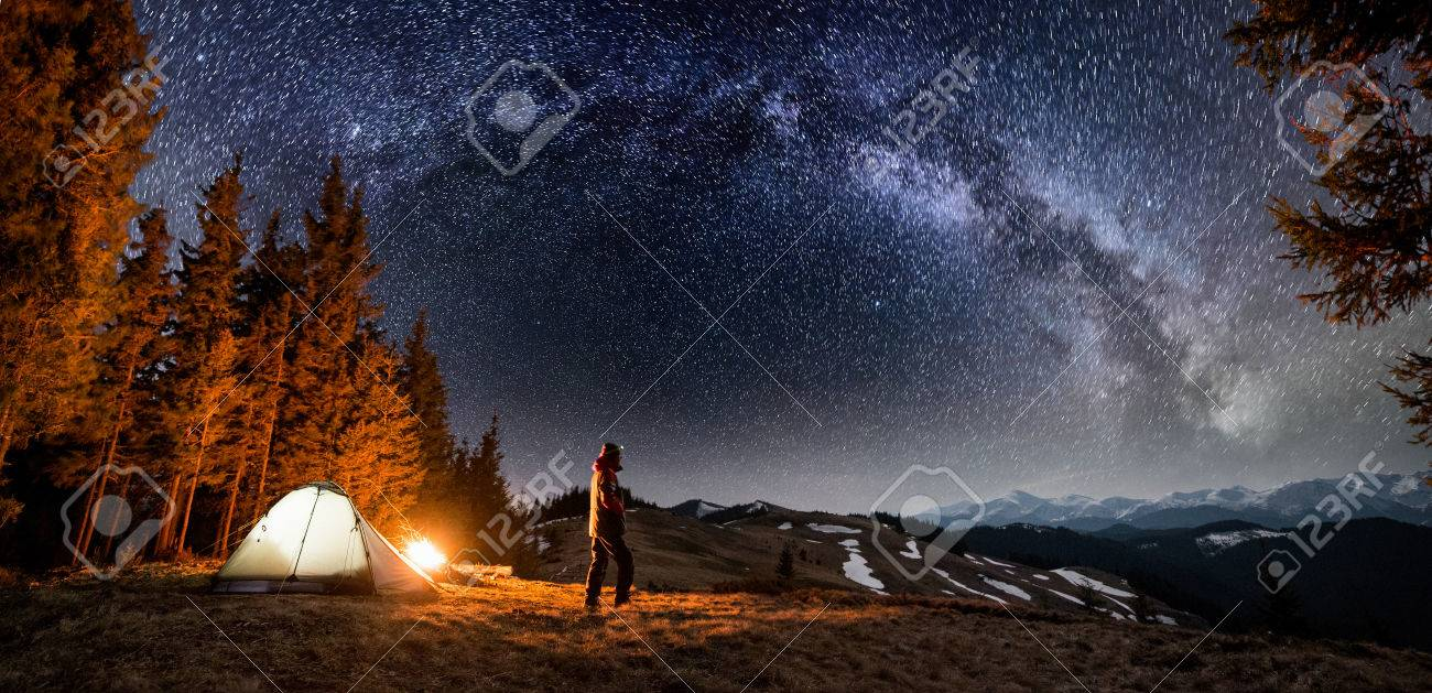 Male tourist have a rest in his camp near the forest at night. Man standing near campfire and tent under beautiful night sky full of stars and milky way, and enjoying night scene. Panoramic landscape - 80627048