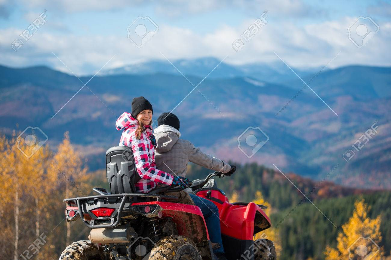 Guy driving ATV, girl sitting behind him and turned around, looking at the camera and smiling. Beautiful landscape mountains at autumn sunny day on blurred background - 80717329