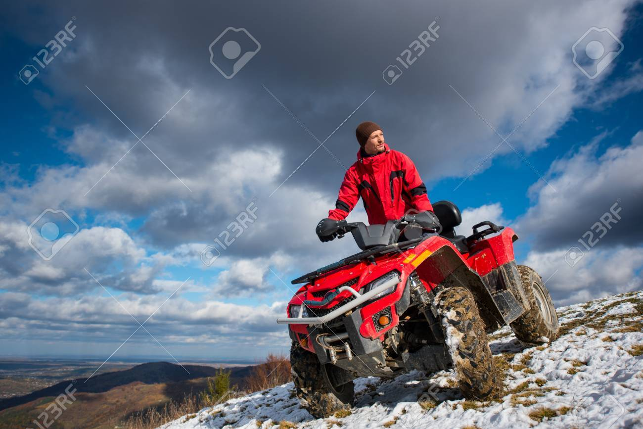 Bottom view of a guy on the sports atv quad bike at the snow-covered slope against the blue cloudy sky on a sunny day in the mountains - 80717334