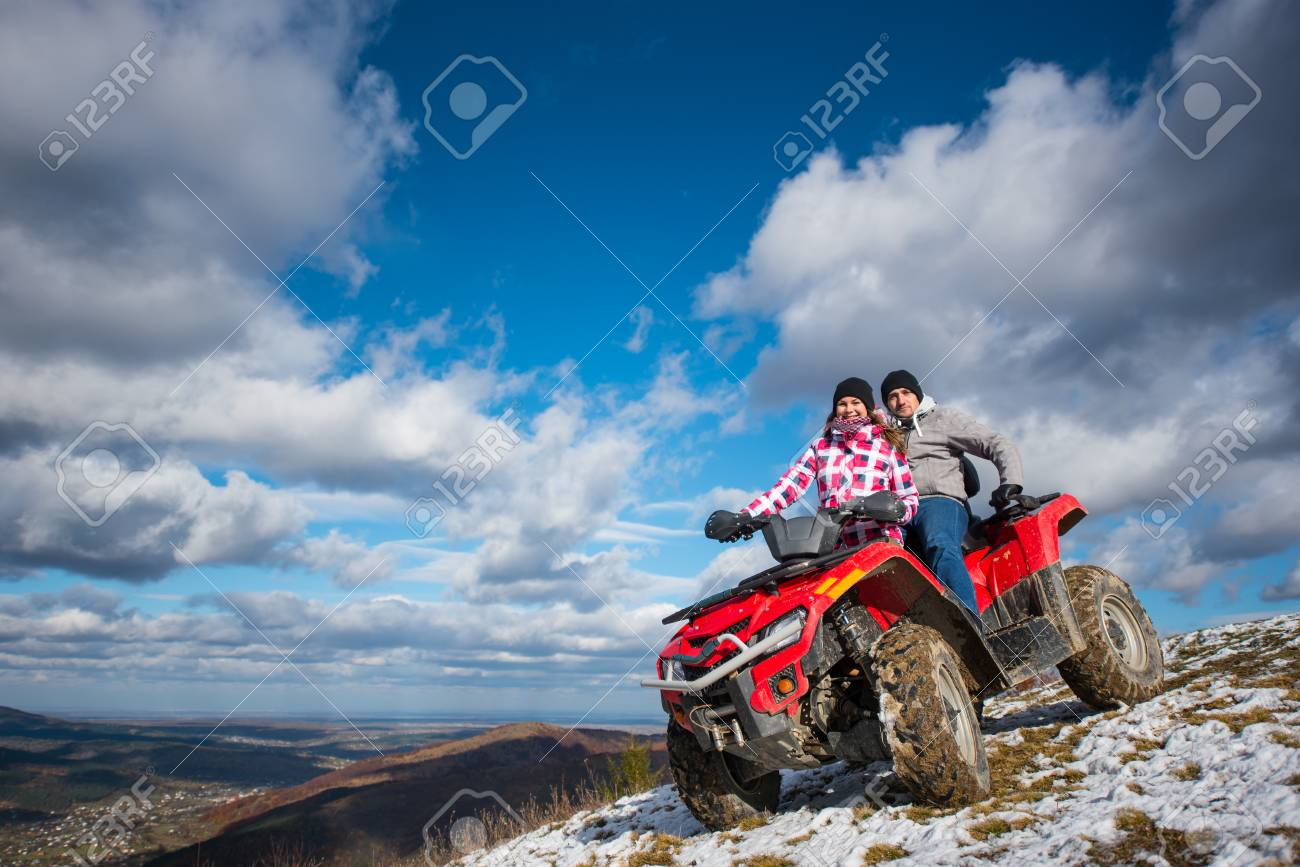 Smiling couple in winter clothes on a red quad bike on a mountain slope under the blue cloudy sky on background of mountains and the town in the valley - 80765953