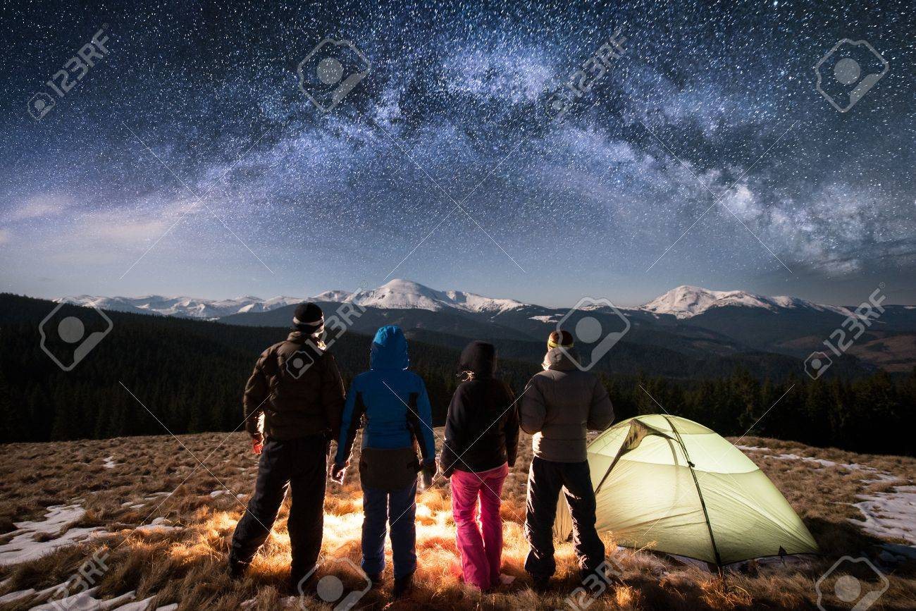 Silhouette of four people standing together beside camp and tent under beautiful night sky full of stars and milky way. On the background snow-covered mountains. Rear view. Long exposure - 86858935
