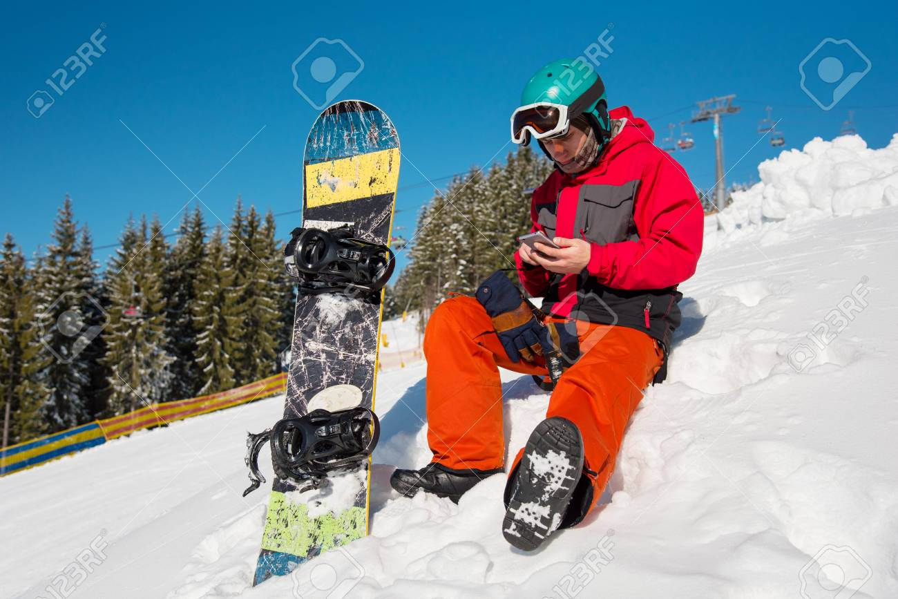 snowboarder sitting in the snow at ski resort,using his smart