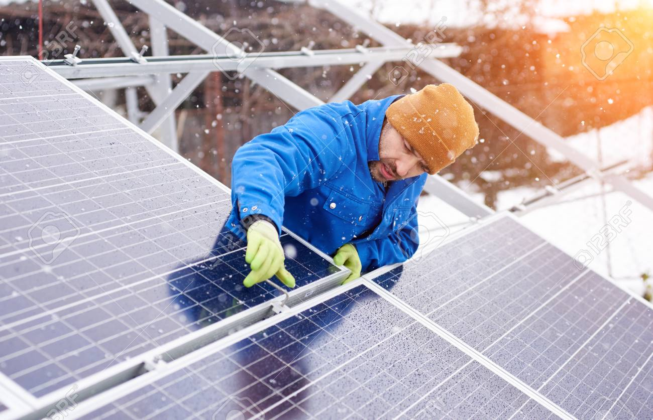 Guy with the help of tools installs solar panels in snowy weather. He is dressed in uniform and gloves - 98231008