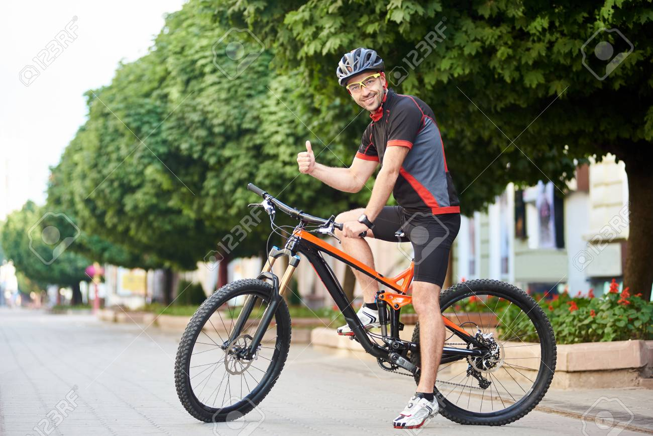 Happy man cyclist in professional cycling clothing and protective garment  showing thumbs up sitting on bicycle e93e50c08