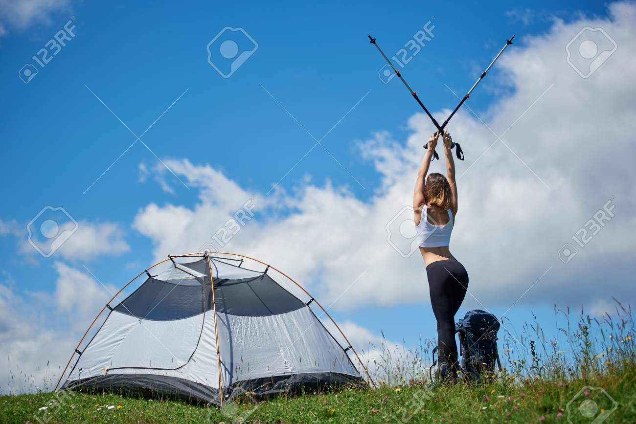 Back view of sporty sexy hiker with backpack near tent on the top of a hill against blue sky and clouds lifting hands up in the air with trekking sticks in ... & Back View Of Sporty Sexy Hiker With Backpack Near Tent On The ...