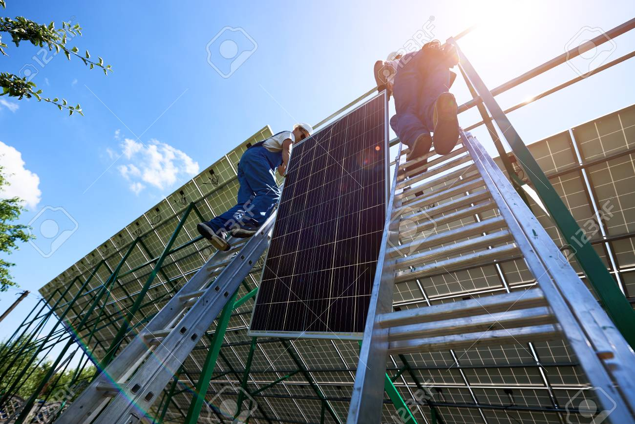 Professional workers team installing solar panels on the green metal construction using different equipment. Innovative solution for energy solving. Use renewable resources. Green energy. - 107253827