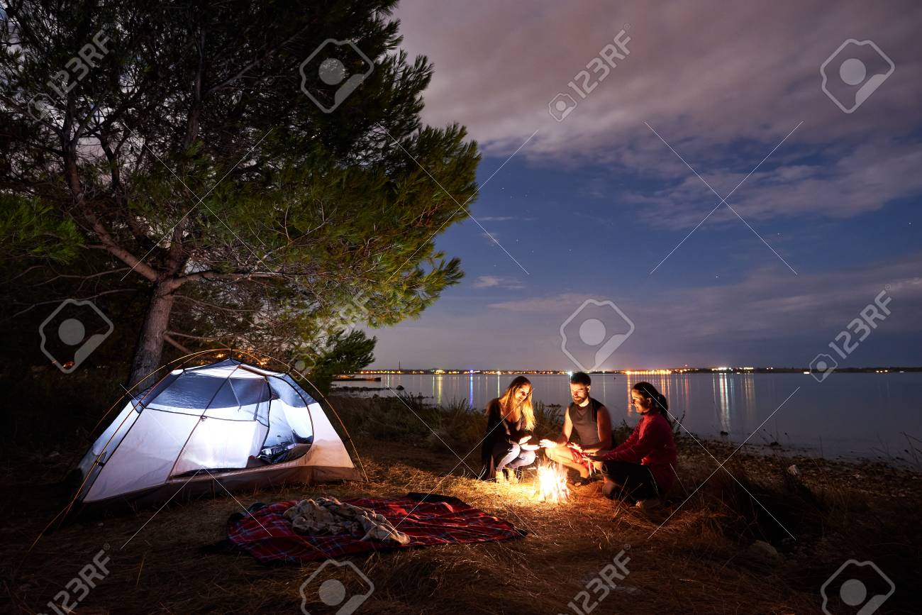 Group of three tourists, young man and women sitting on lake shore at bonfire near tourist tent under tree. Quiet water surface and evening sky on background. Tourism, friendship and camping concept. - 107500927