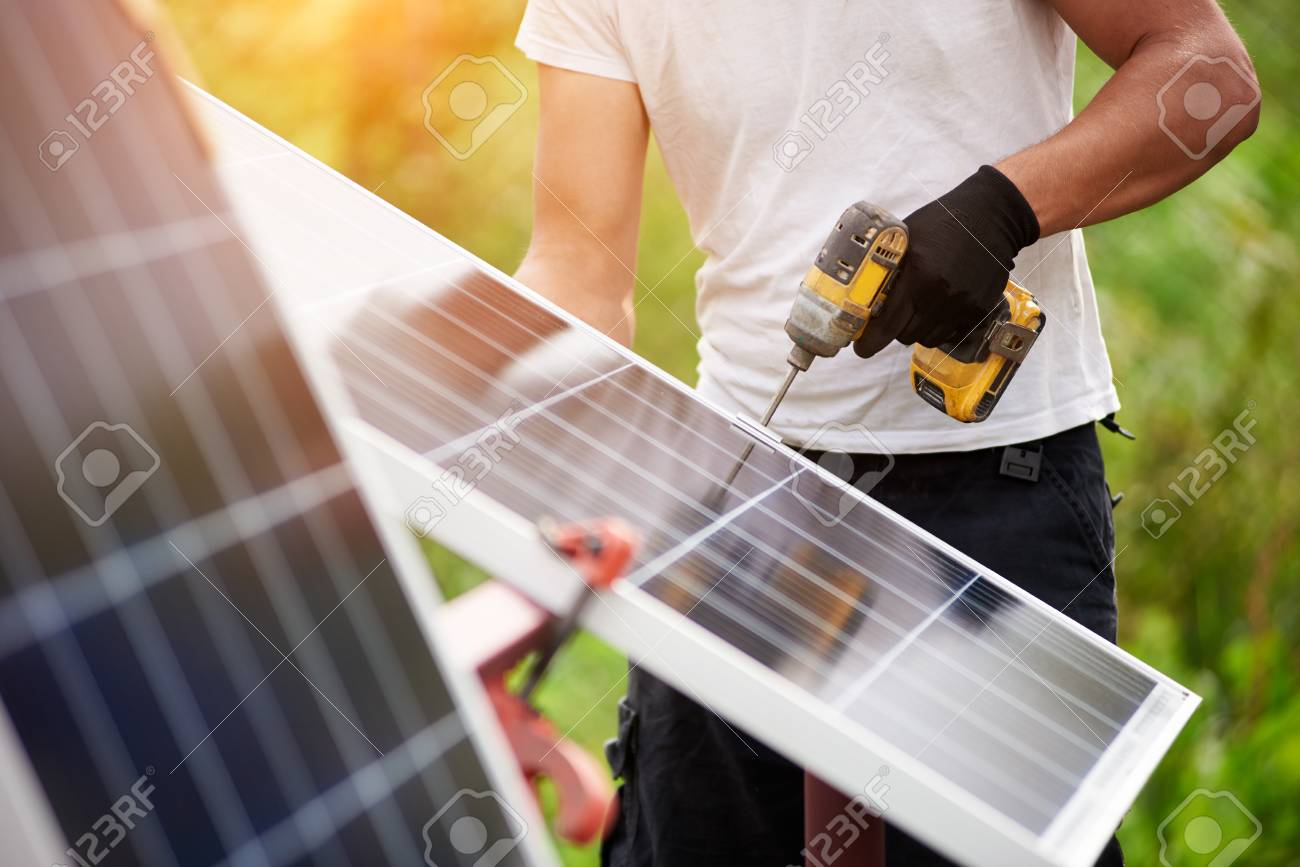 Technician worker assembling shiny solar photo voltaic panels using electrical screwdriver standing outdoors on bright green sunny colorful blurred bokeh background. Efficiency and professionalism. - 108062099