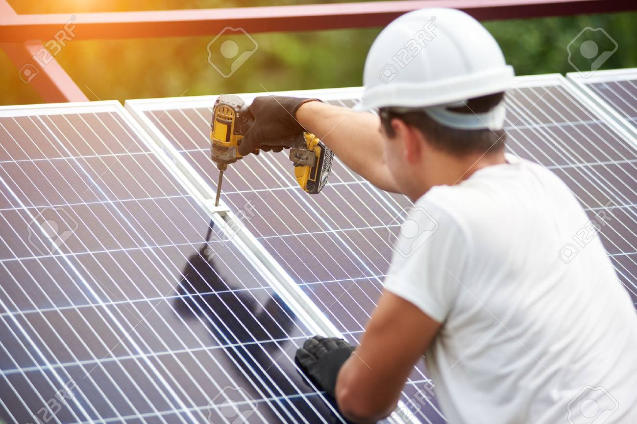 Back view of young technician in helmet connecting solar photo voltaic panel to metal platform using electrical screwdriver on shiny surface background. Stand-alone solar panel system installation. - 110515957