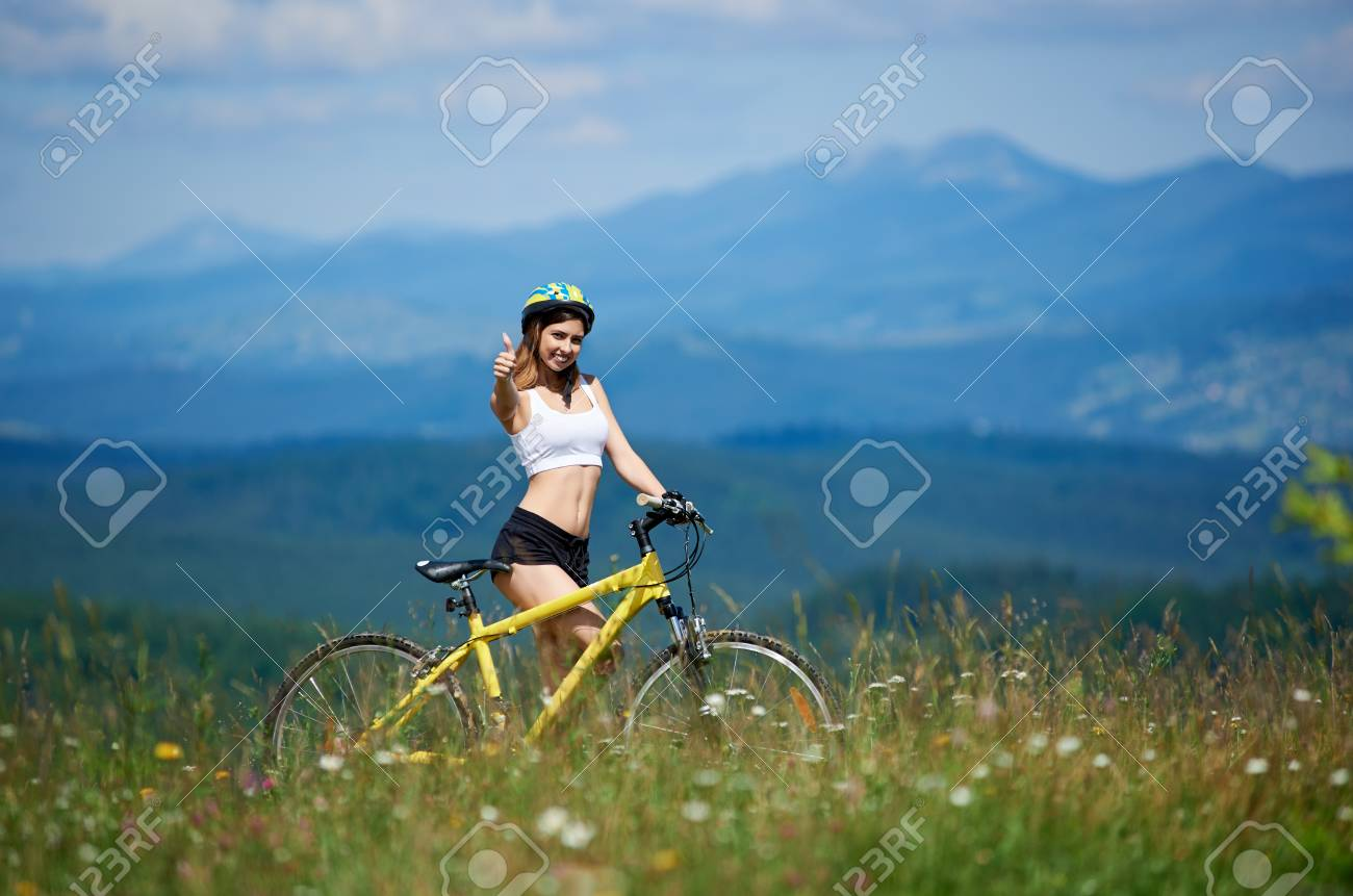 Happy Young Woman Rider With Yellow Mountain Bike Smiling To