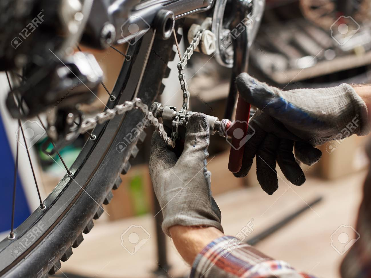 Cropped shot of male mechanic making service in bicycle repair