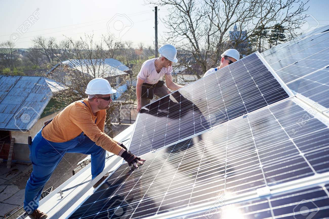 Male workers installing solar photovoltaic panel system. Electricians mounting blue solar module on roof of modern house. Alternative energy ecological concept. - 120141569