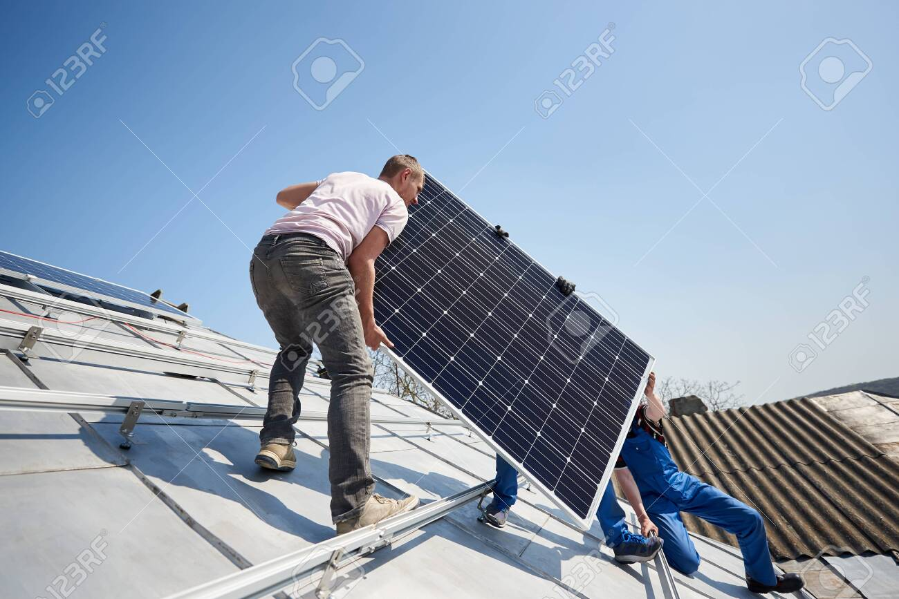 Male workers installing stand-alone solar photovoltaic panel system. Electricians lifting blue solar module on roof of modern house. Alternative energy sustainable resources renewable concept. - 121323551