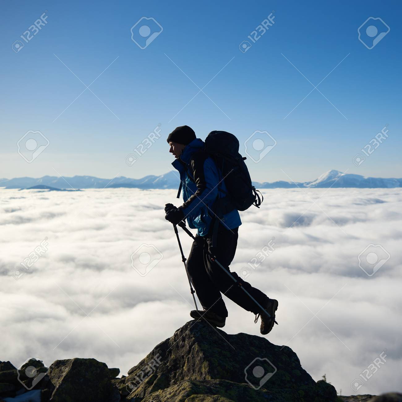 Tourist man with backpack and hiker sticks standing on top of big rock on background of bright blue sky, foggy valley filled with white clouds and distant mountain tops covered with first snow. - 121323557