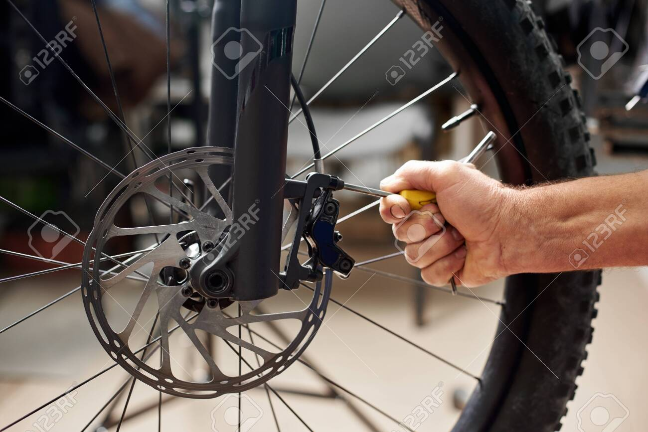 Cropped shot of male mechanic working in bicycle repair shop,
