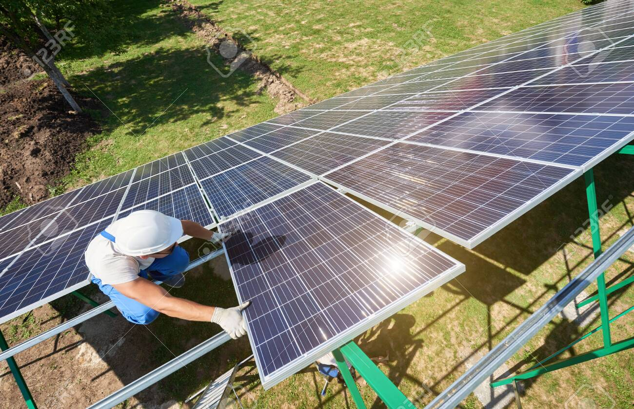 Professional worker installing solar panels on the green metal construction, using different equipment, wearing helmet. Innovative solution for energy solving. Use renewable resources. Green energy. - 123414557