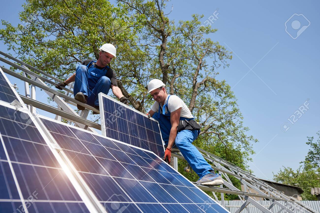 Two young technicians mounting heavy solar photo voltaic panel on tall steel platform on green tree background. Exterior solar panel voltaic system installation, dangerous job concept. - 130205847