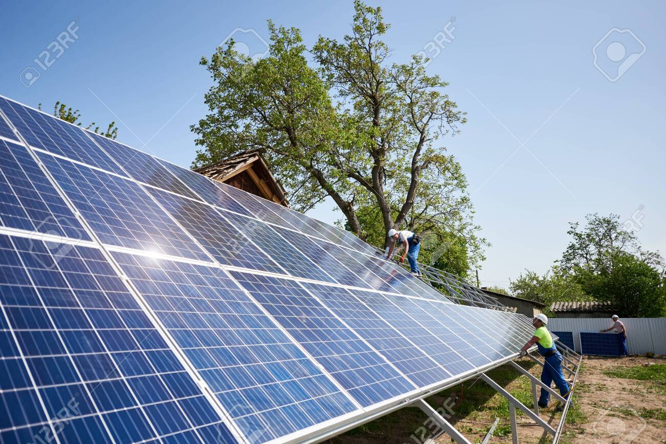 Two technicians installing solar panel photo voltaic system installation on steel platform on bright sunny summer day under blue sky. Renewable ecological green energy production concept. - 131580935