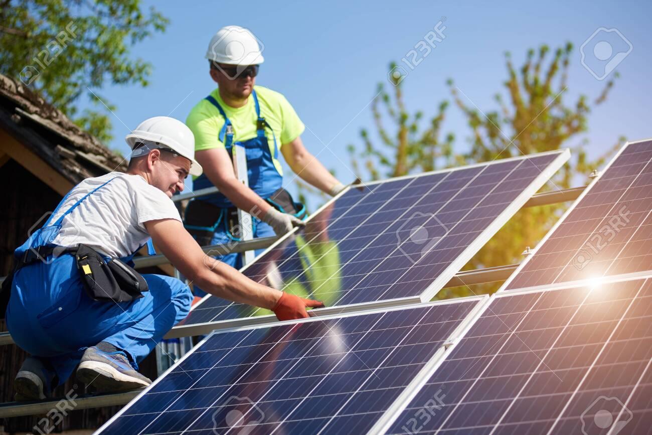 Two professional technicians installing heavy solar photo voltaic panels to high steel platform. Exterior solar system installation, alternative renewable green energy generation concept. - 137435656