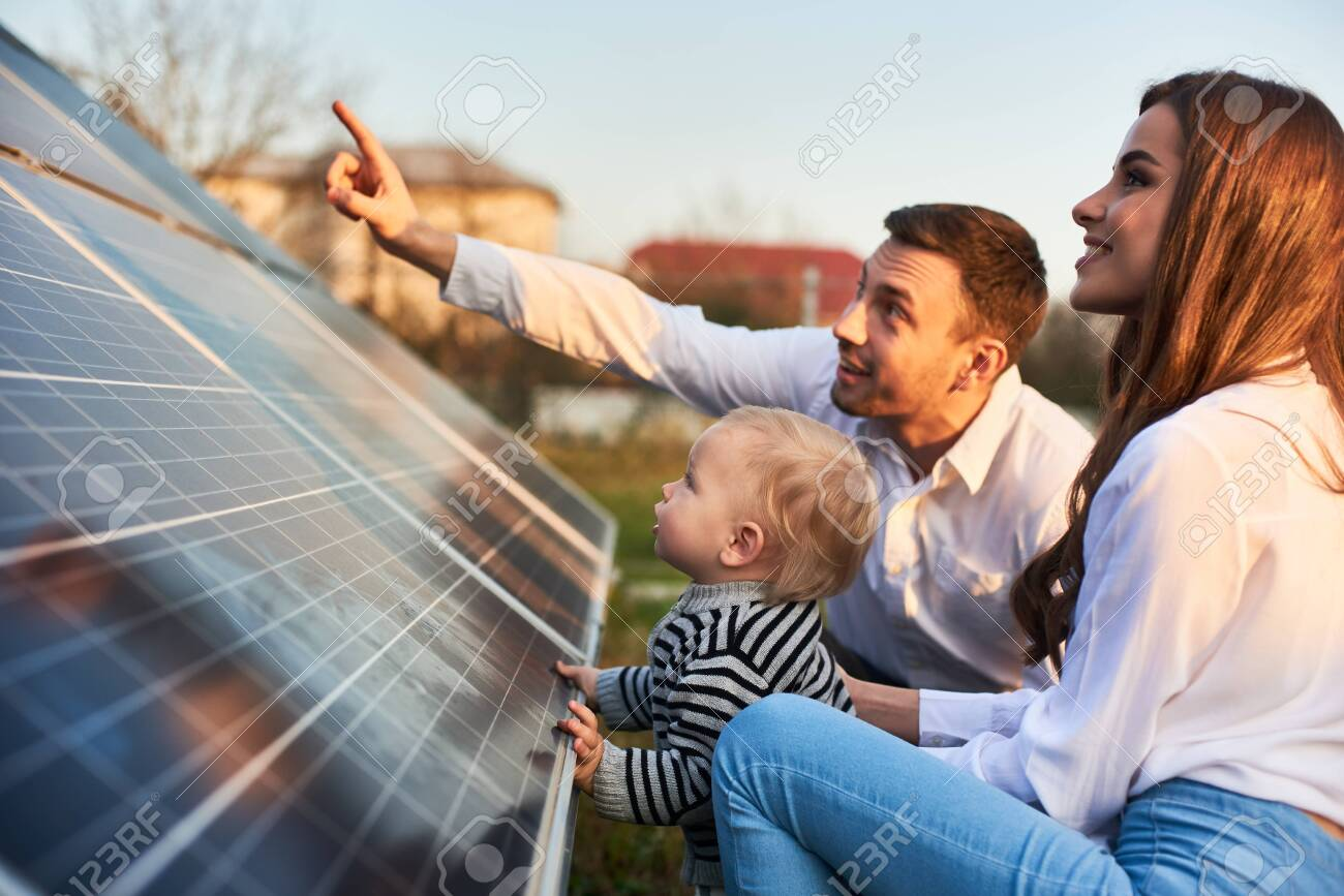 Man shows his family the solar panels on the plot near the house during a warm day. Young woman with a kid and a man in the sun rays look at the solar panels. - 142382317