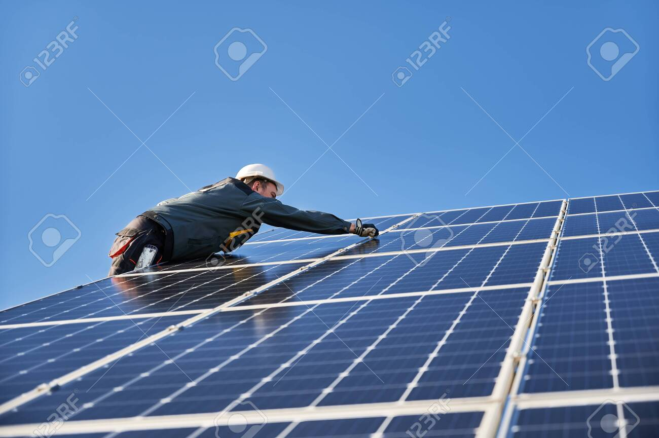 Male worker mounting solar modules, panels and support structures of photovoltaic solar array. Electrician wearing safety helmet and gloves. Concept of sun energy and power sustainable resources. - 147235635